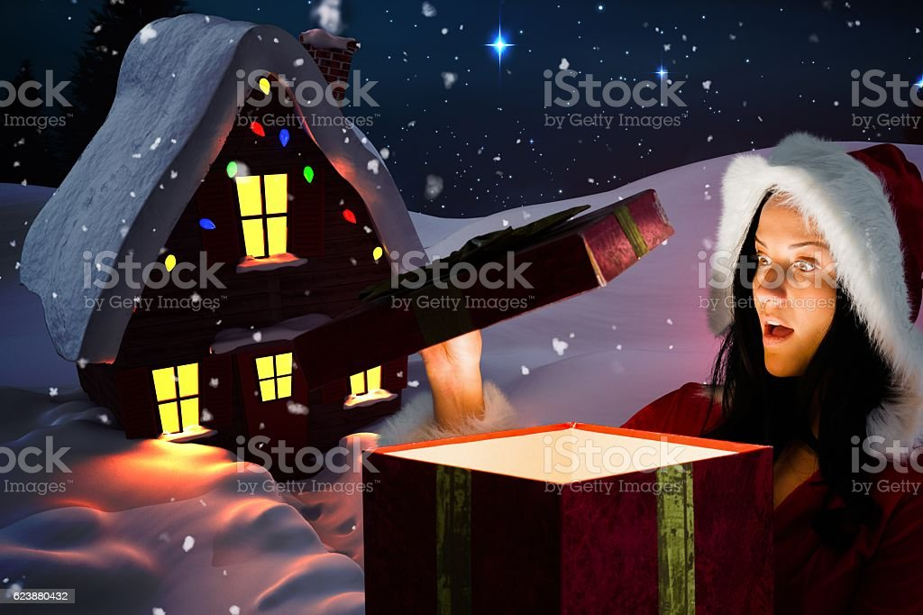 Woman in santa costume looking at christmas gift stock photo