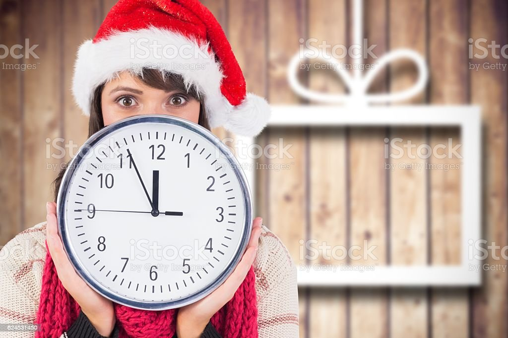 Woman in santa hat covering her face behind clock stock photo