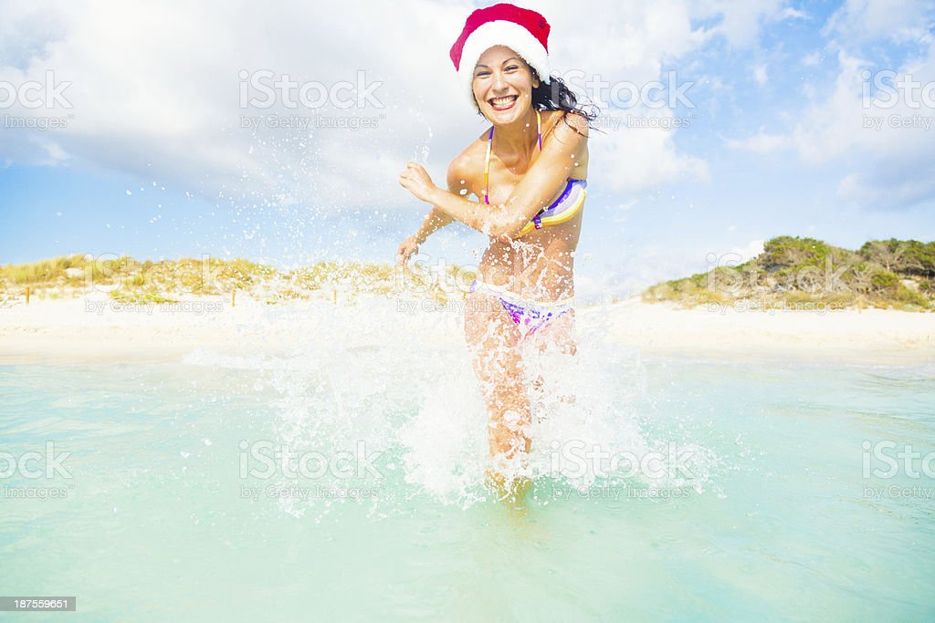 woman in santa hat having fun by the sea royalty-free stock photo