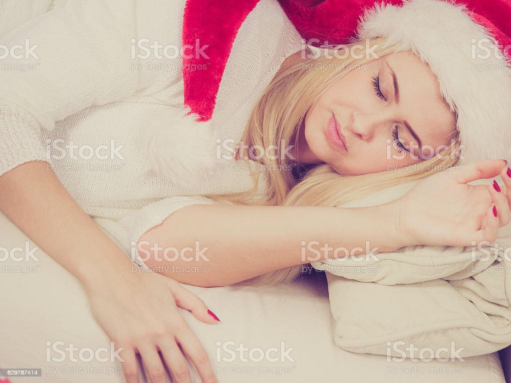 Woman in Santa hat sleeping on couch stock photo