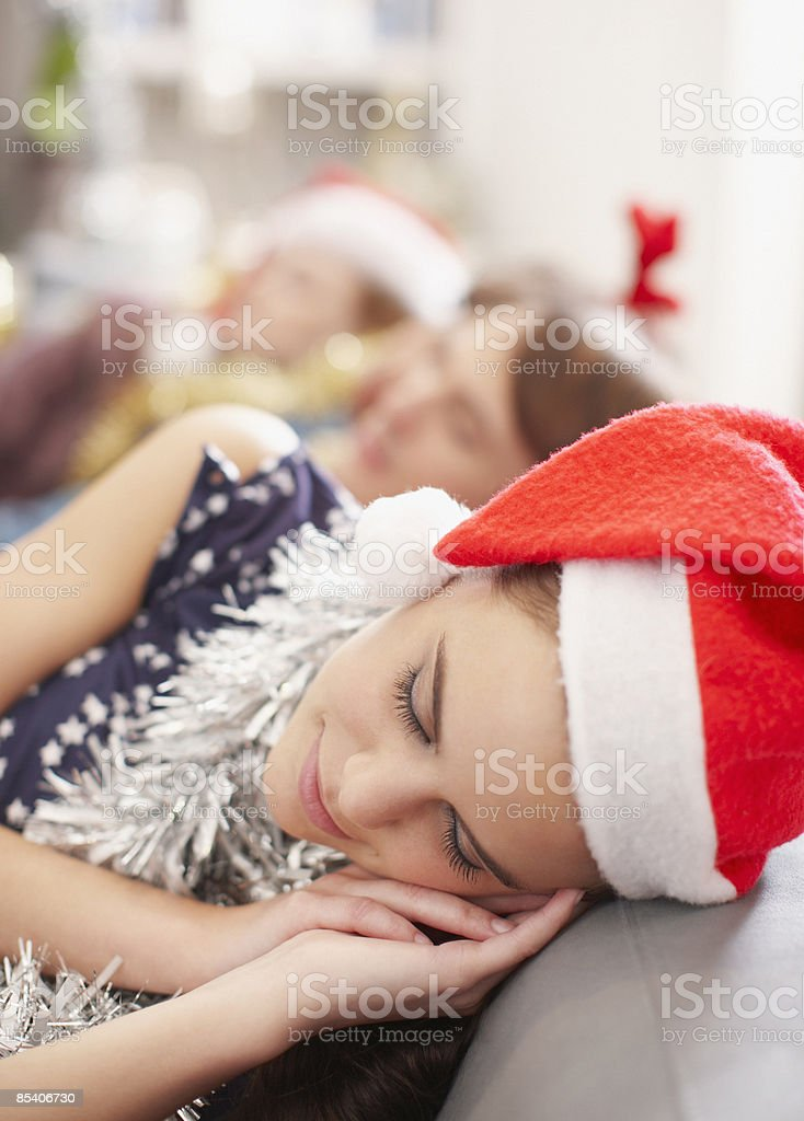 Woman in Santa hat sleeping on sofa royalty-free stock photo