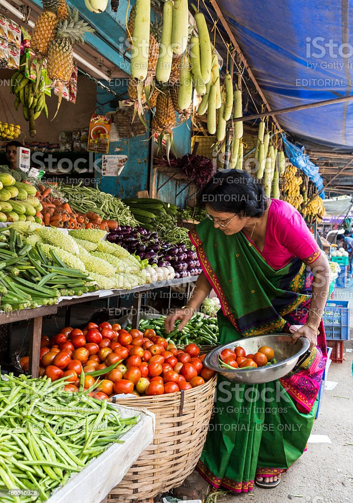 Woman in sari selects vegetables in market in Kochi stock photo