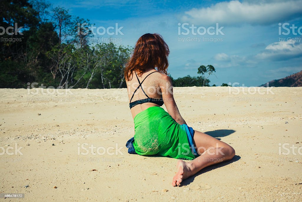 Woman in sarong sitting on tropical beach stock photo