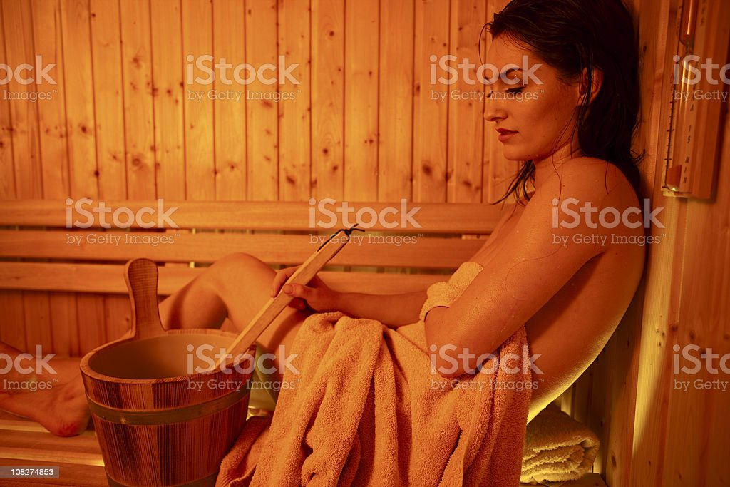 Woman in Sauna with Water Bucket royalty-free stock photo
