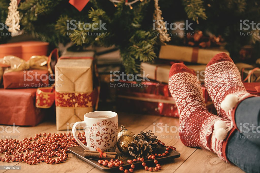 Woman\'s legs in seasonal socks and Christmas decoration in front of...