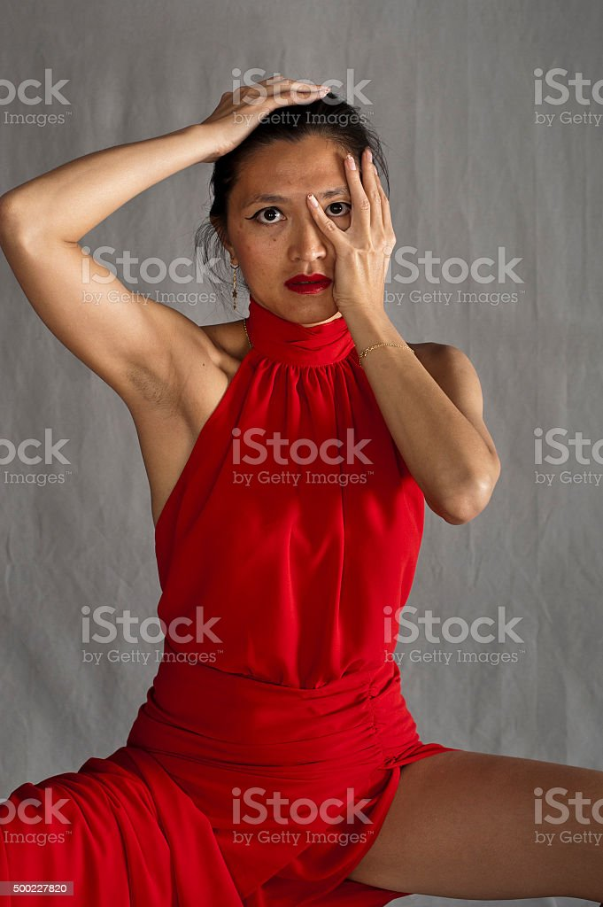 Woman in seated red dress stock photo