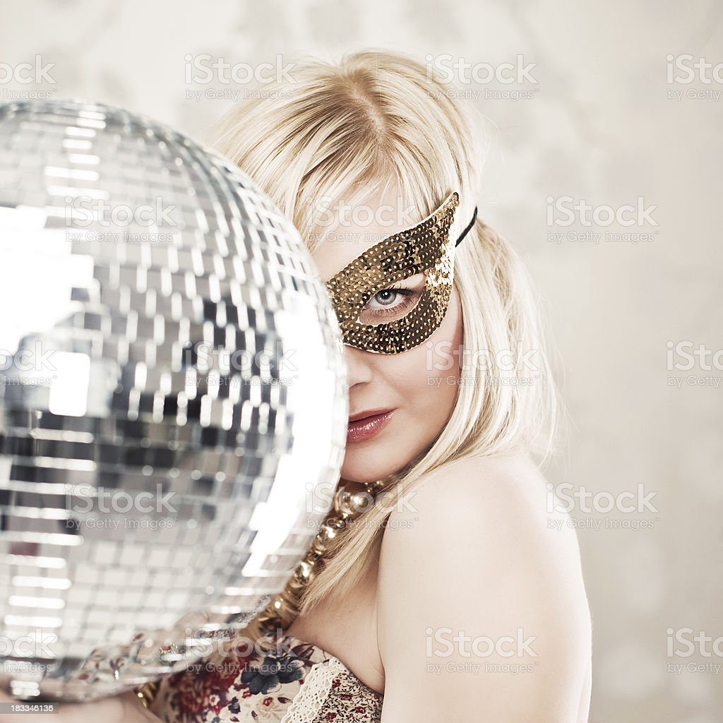 Woman in sequin disguise and disco ball stock photo