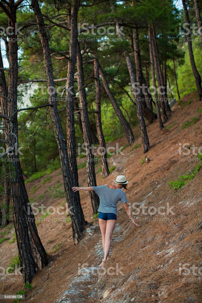 woman in shorts and hat walking the summer forest stock photo