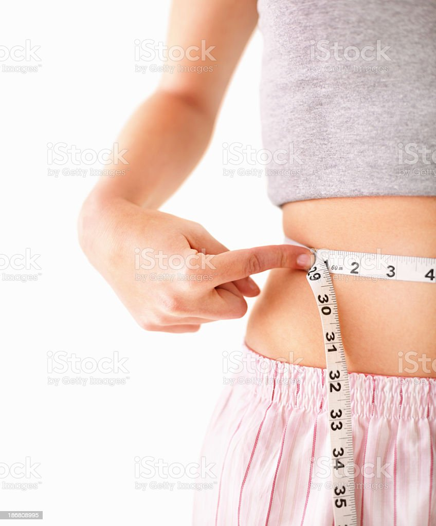 Woman in shorts and t-shirt with measuring tape around waist royalty-free stock photo