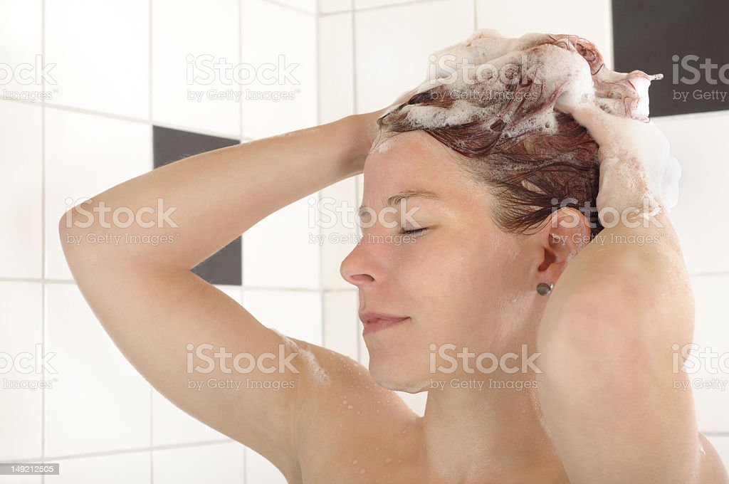Woman in shower washing and lathering her hair royalty-free stock photo