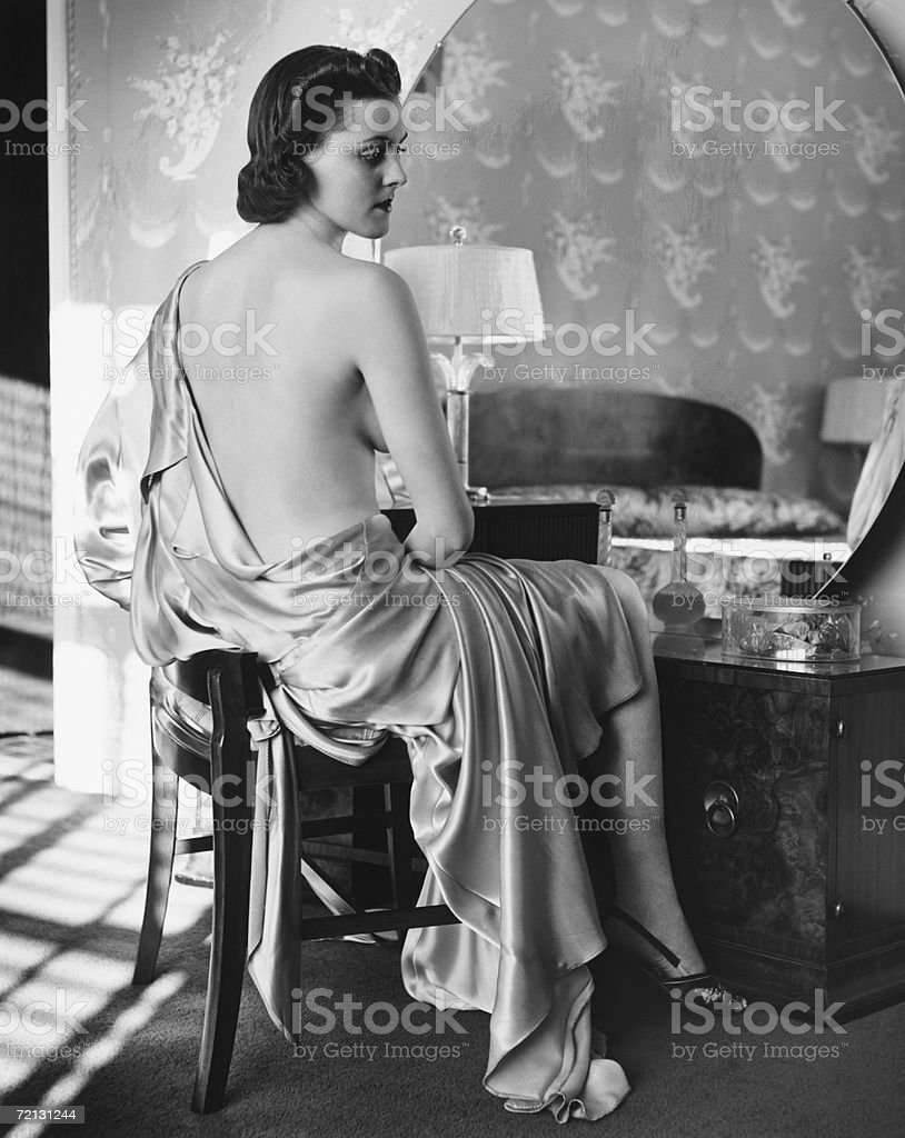 Woman in silk bathrobe sitting in front of vanity table (B&W) royalty-free stock photo