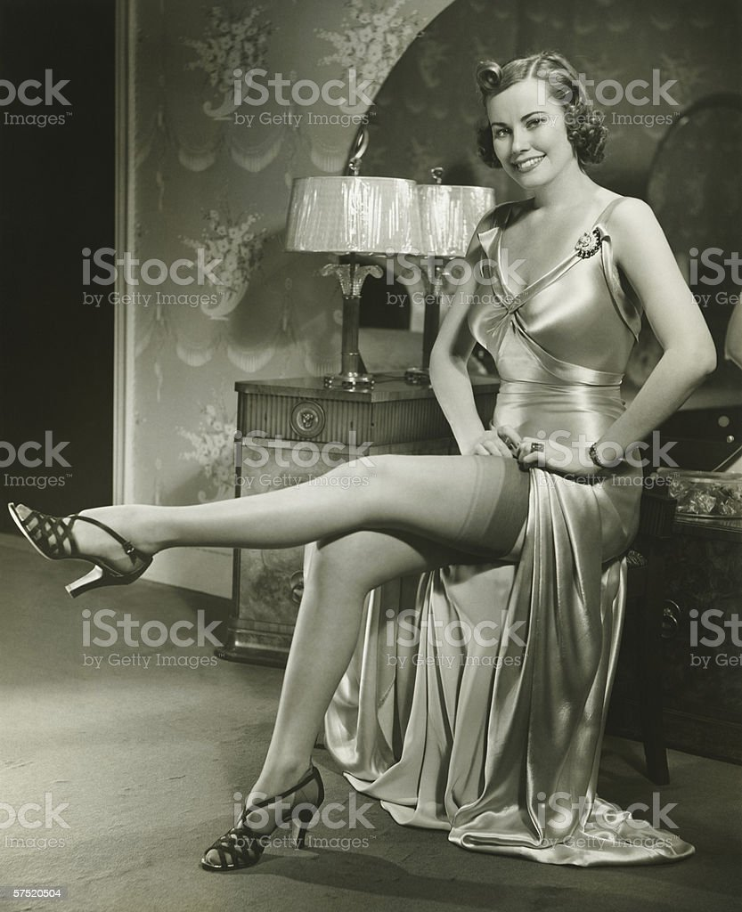 Woman in silk evening gown sitting by vanity table, showing leg, (B&W) stock photo