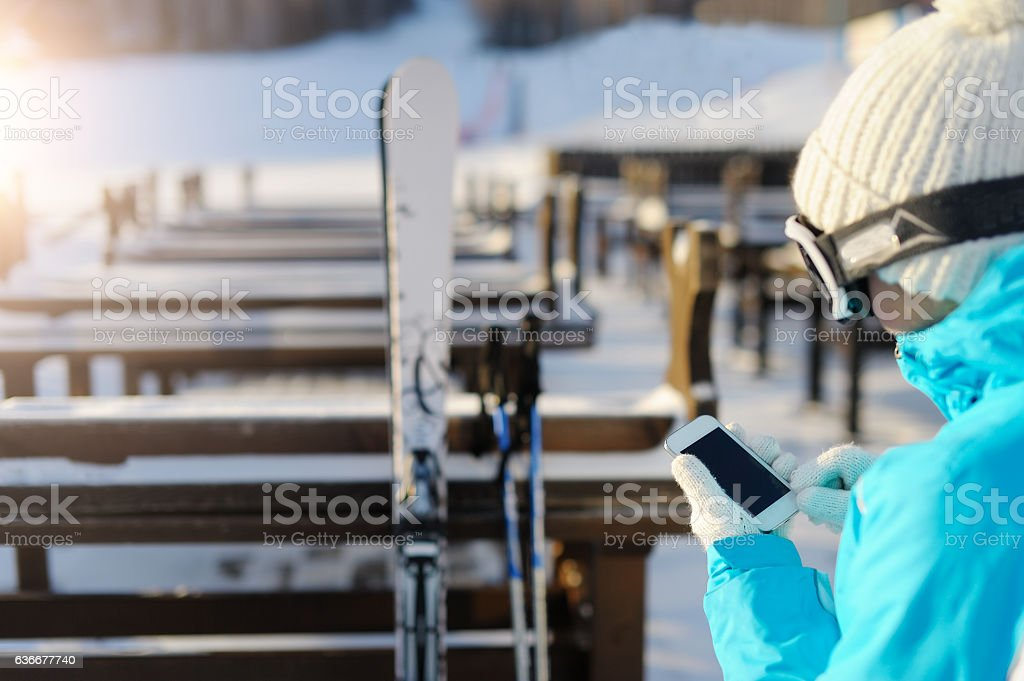 Woman in ski glasses holding a smartphone. stock photo