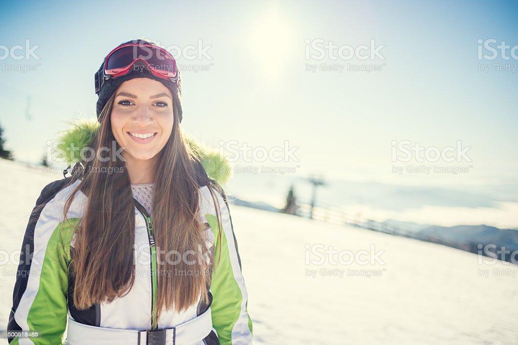 Woman in ski wear on the top of mountain stock photo