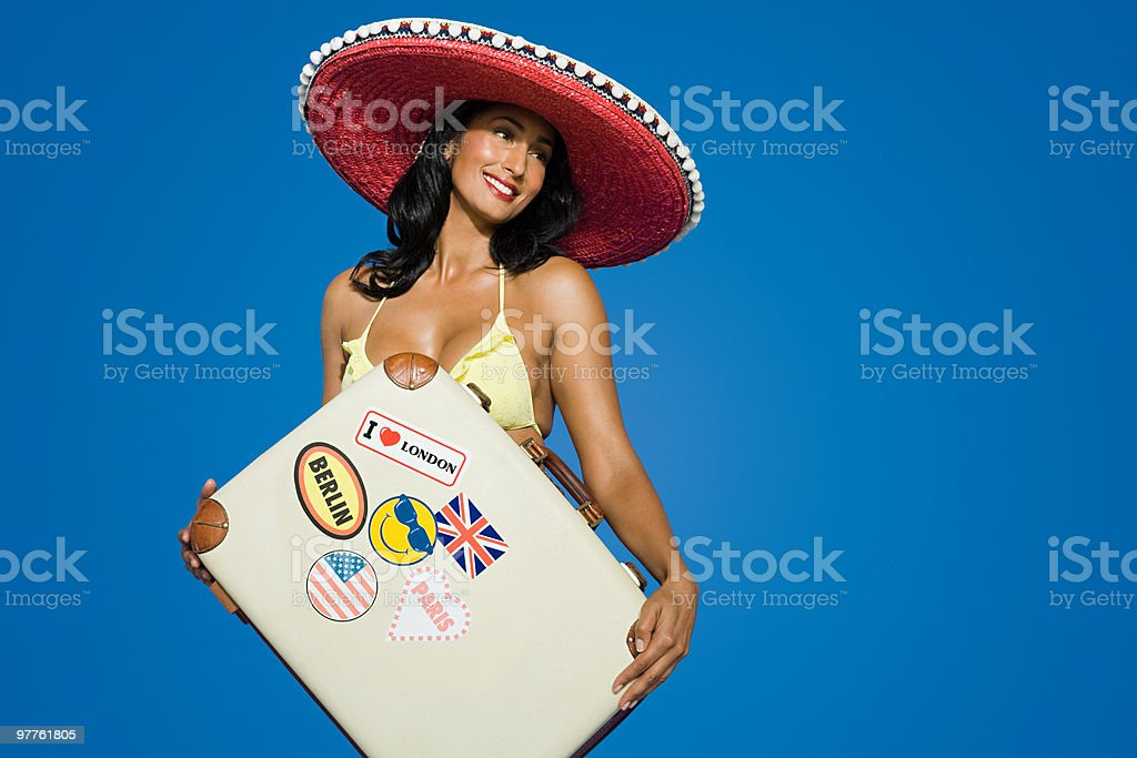 Woman in sombrero with suitcase stock photo