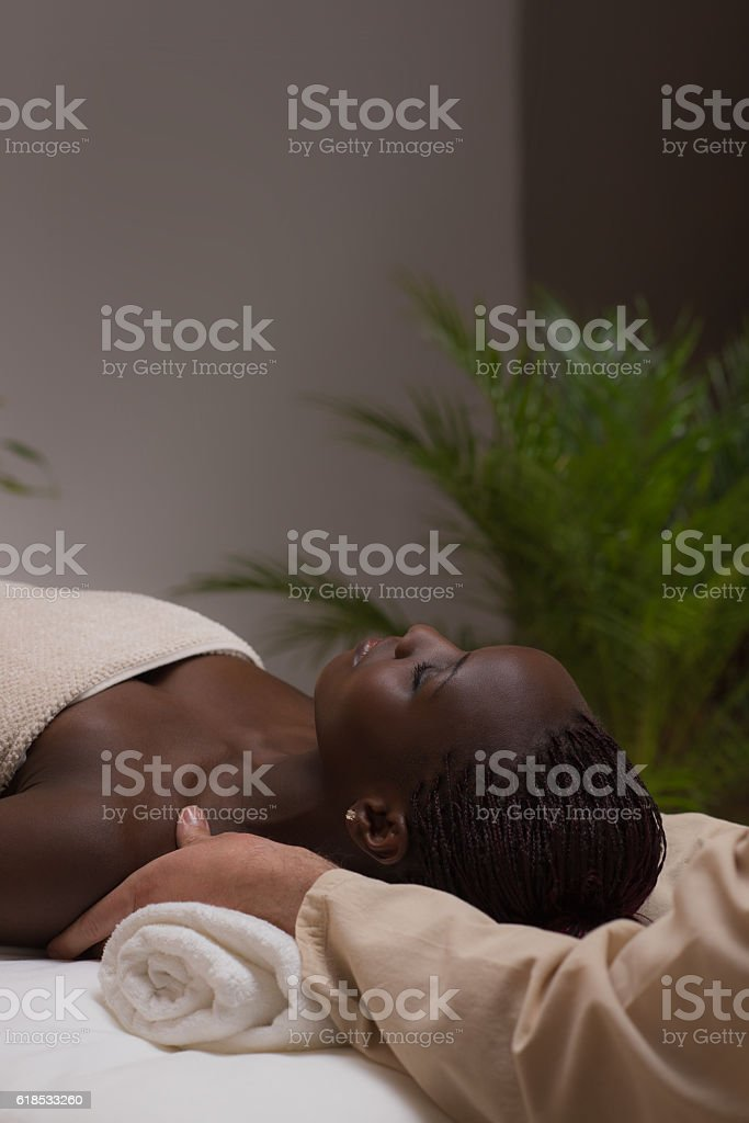Woman in spa environment getting massage stock photo
