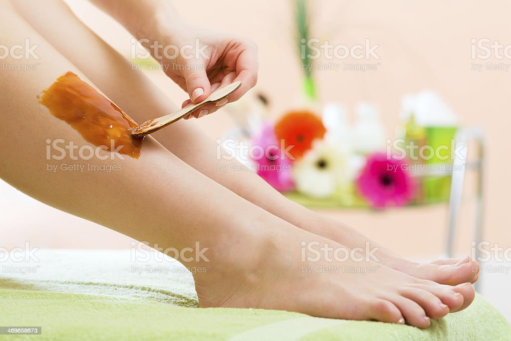 Woman in Spa getting leg waxed for hair removal stock photo