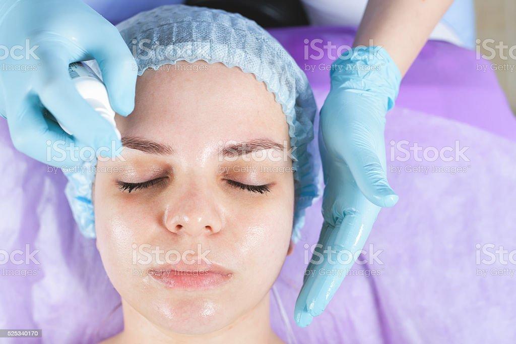 Woman in spa salon receiving face treatment with facial cream stock photo