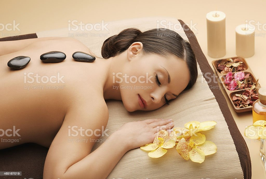 Woman in spa with hot rocks on back  stock photo