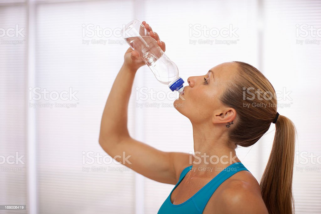 Woman in sports bra drinking water stock photo