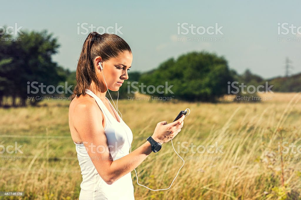 Woman in sports clothes is busy with phone royalty-free stock photo