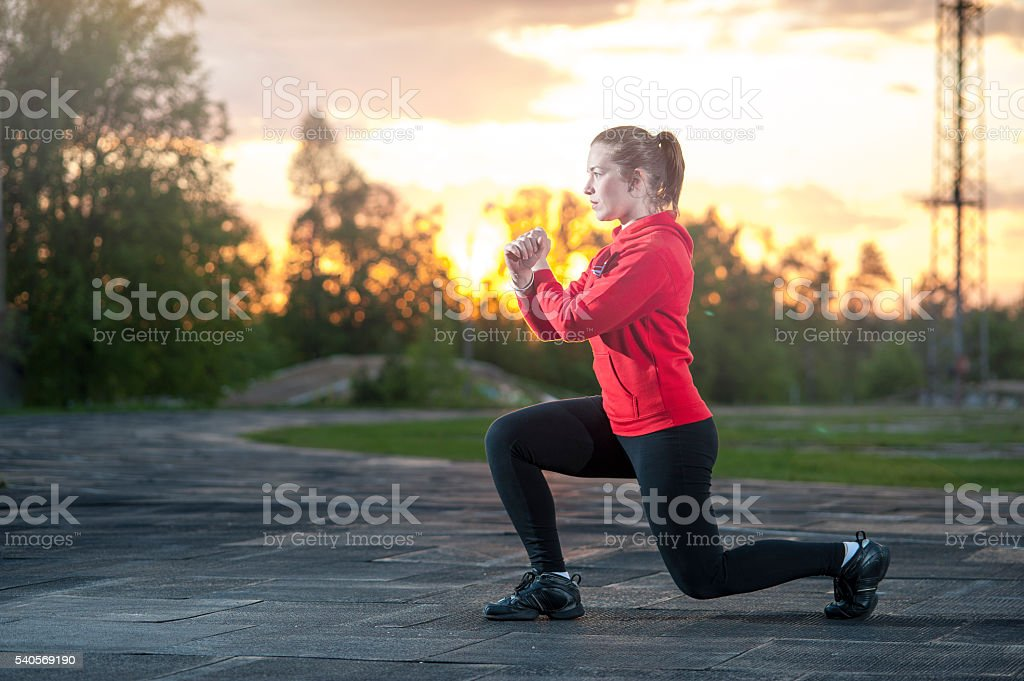 Woman in sportswear doing squats outdoors stock photo