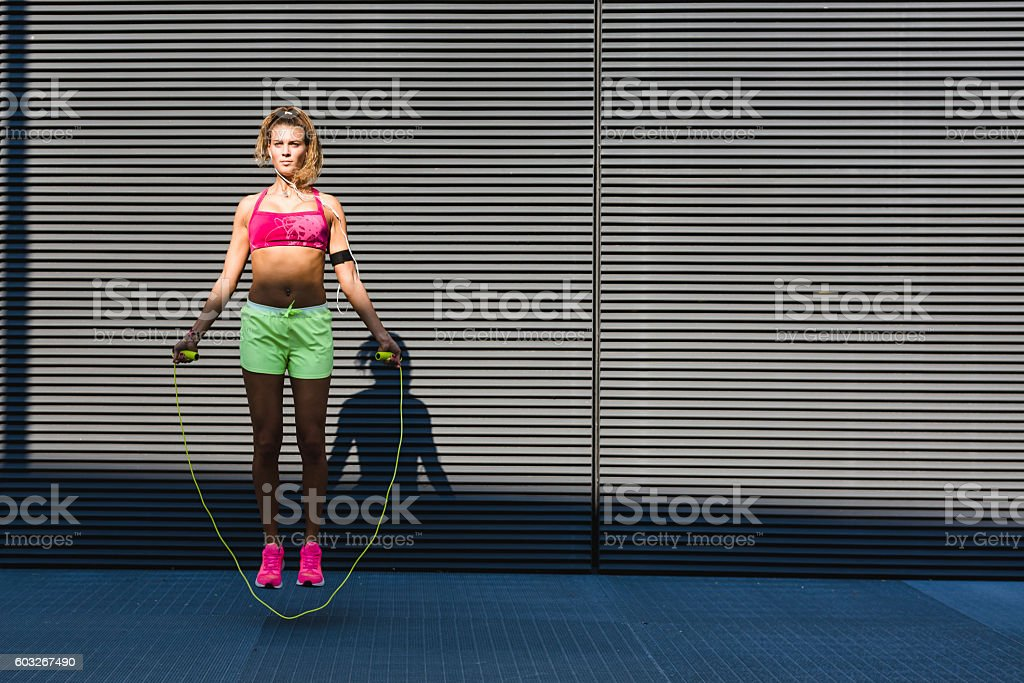 Woman in sportswear doing workout with jumping rope stock photo