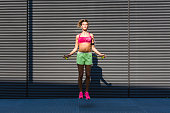 Woman in sportswear doing workout with jumping rope
