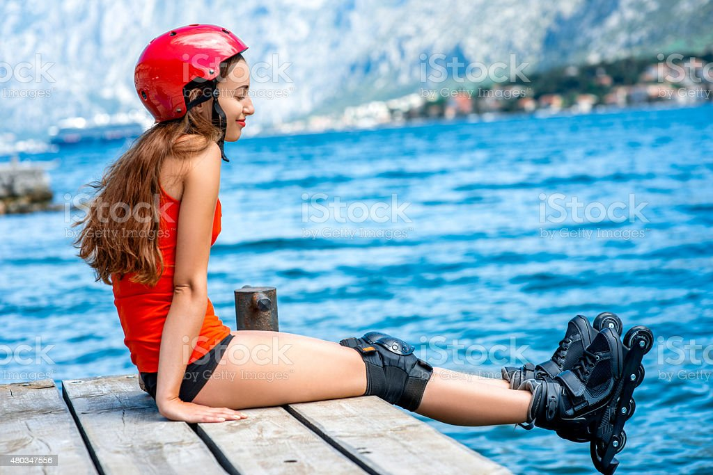 Woman in sportswear with skating rollers on the pier stock photo