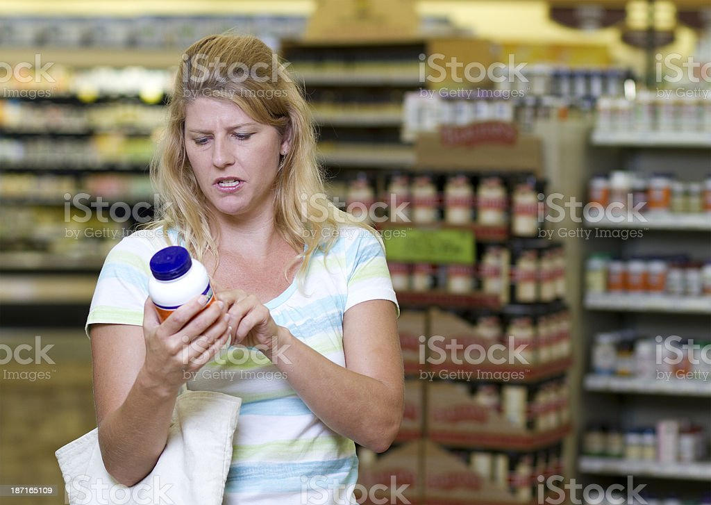 Woman in Store Examines Supplements royalty-free stock photo