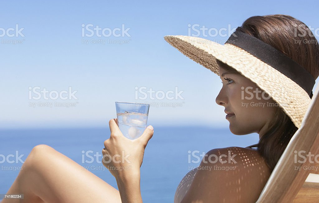 Woman in straw hat sunbathing on wooden chair with beverage royalty-free stock photo