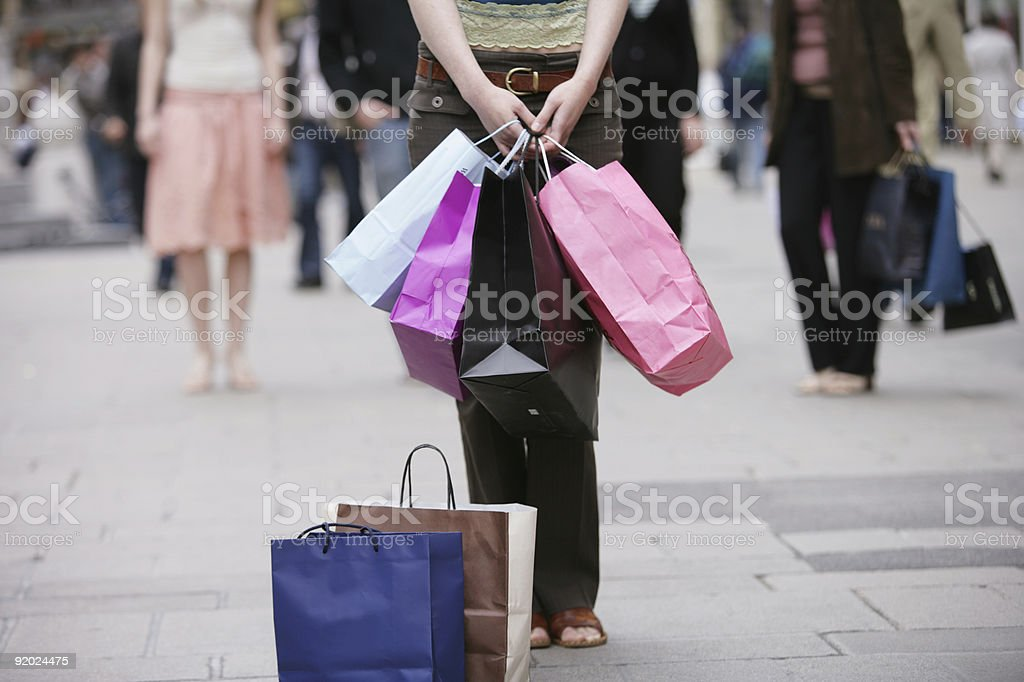 Woman in street carrying shopping bags with more bags around stock photo