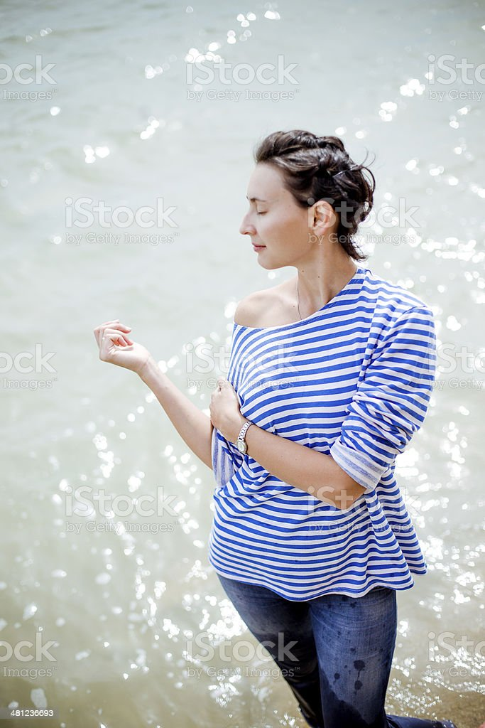 woman in striped blouse on seashore stock photo