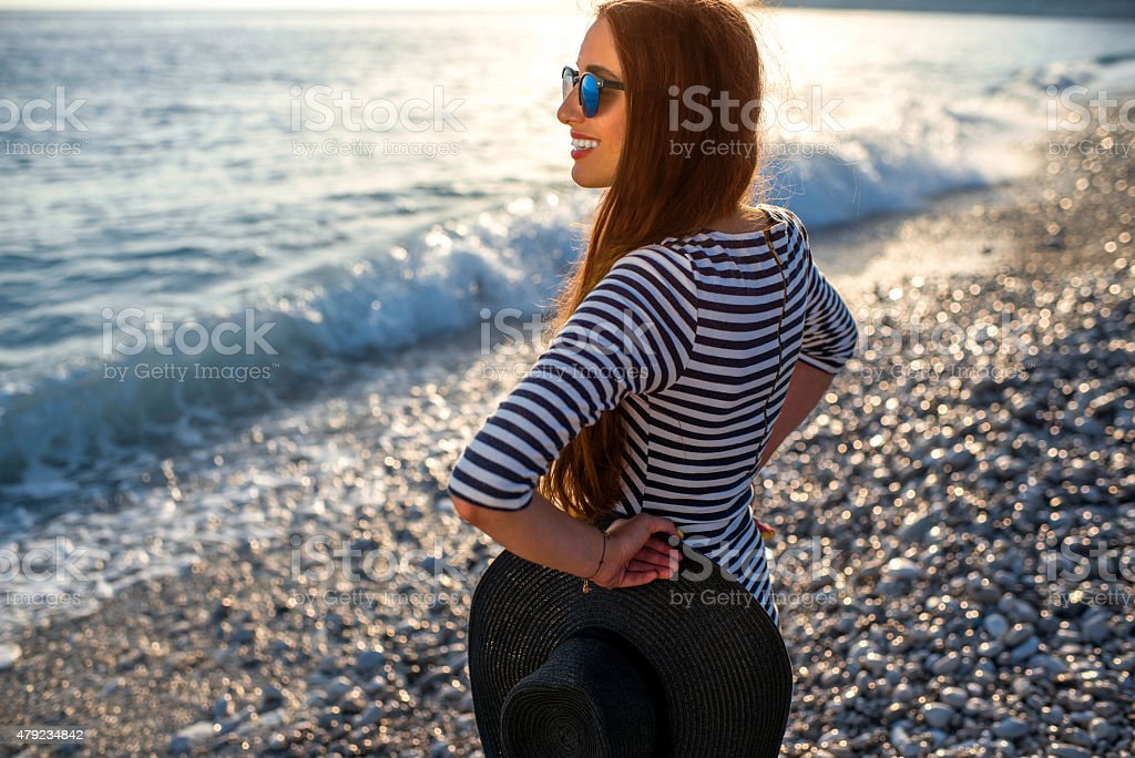 Woman in stripped dress with a hat on the beach stock photo