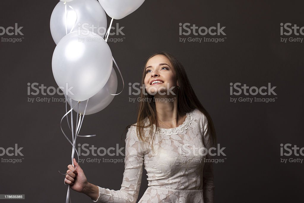 woman in studio with white balloons royalty-free stock photo