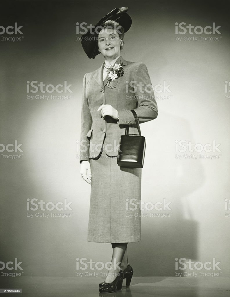 Woman in suit and fashionable hat standing in studio, (B&W) stock photo