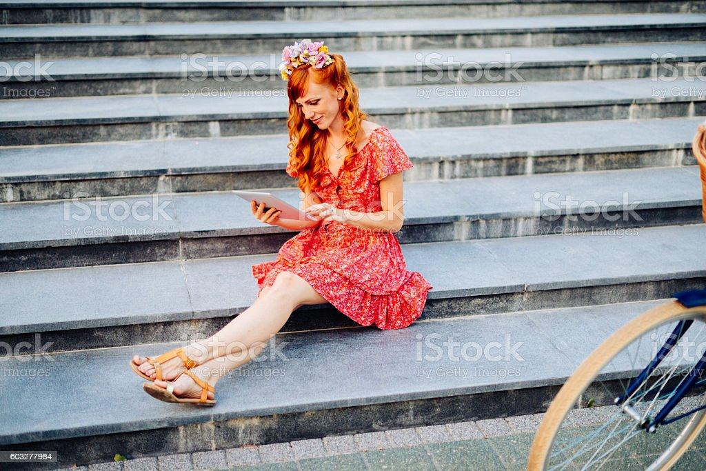 Woman in summer dress using digital tablet stock photo
