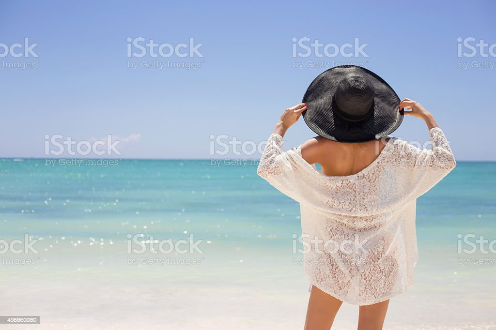 Woman in summer hat on the beach stock photo