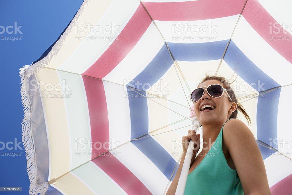 Woman in sunglasses holding beach umbrella royalty-free stock photo