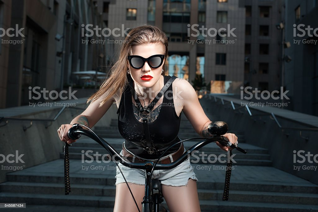 Woman in sunglasses on the bike. stock photo