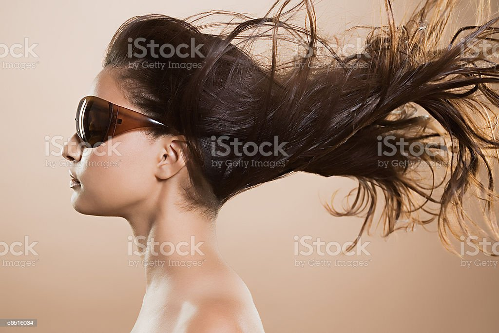 Woman in sunglasses with windswept hair stock photo
