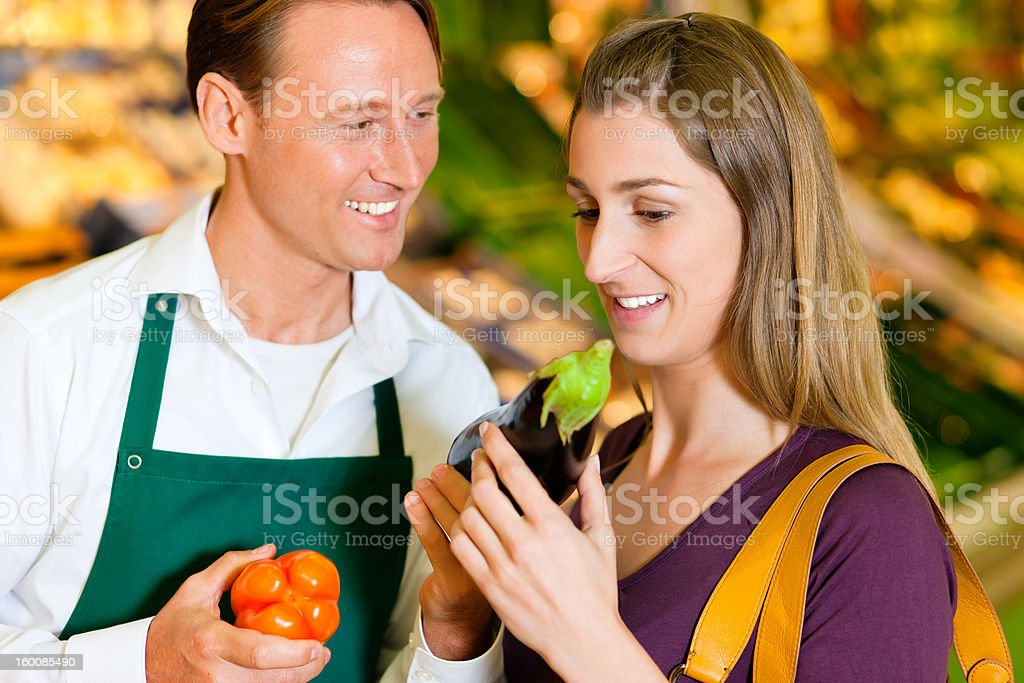 Woman in supermarket and shop assistant royalty-free stock photo