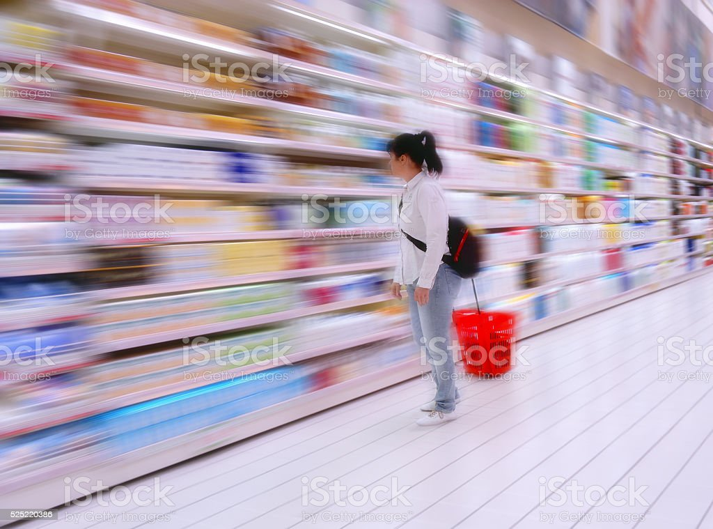 Woman in Supermarket at a shelf with colorful goods stock photo