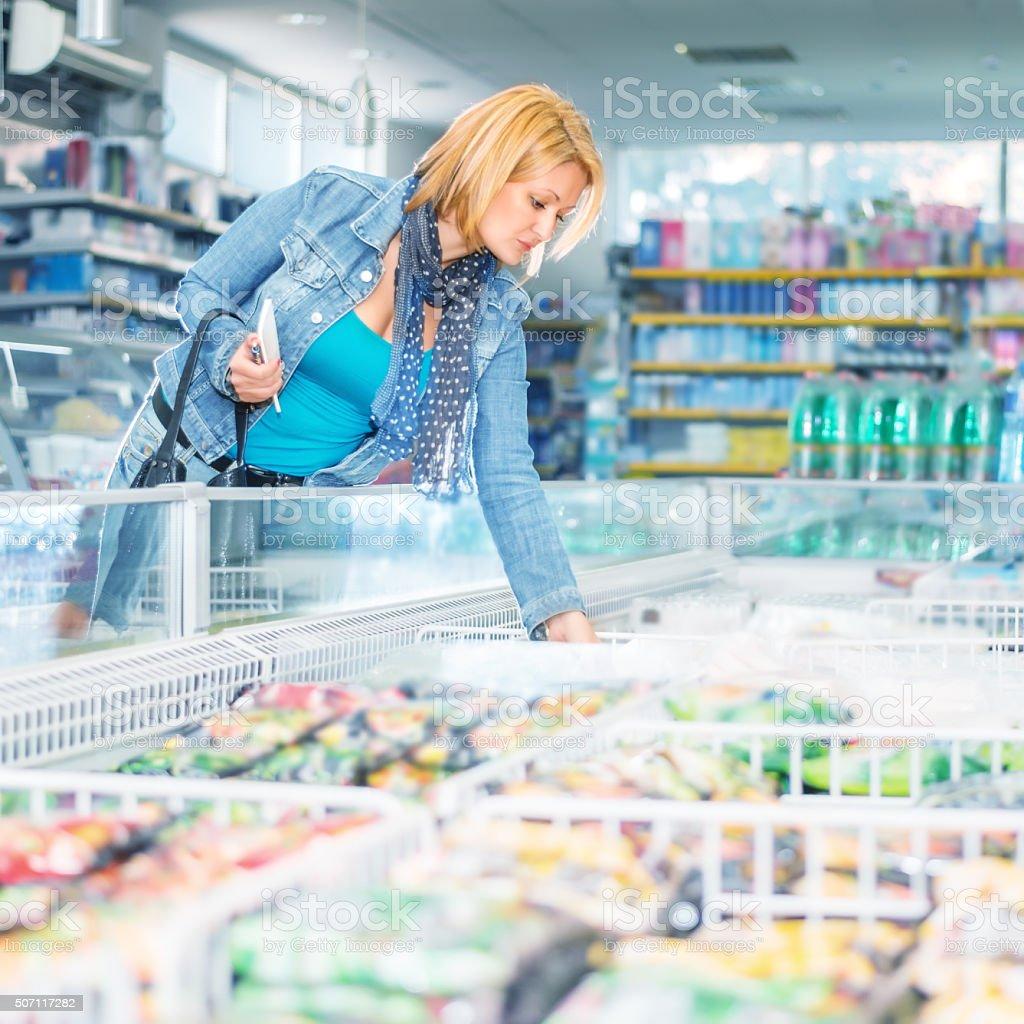 Woman in supermarket near frozen food stock photo