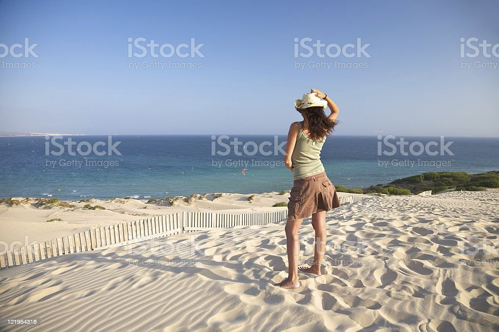 woman in Tarifa beach watching kite surfers in ocean horizon royalty-free stock photo