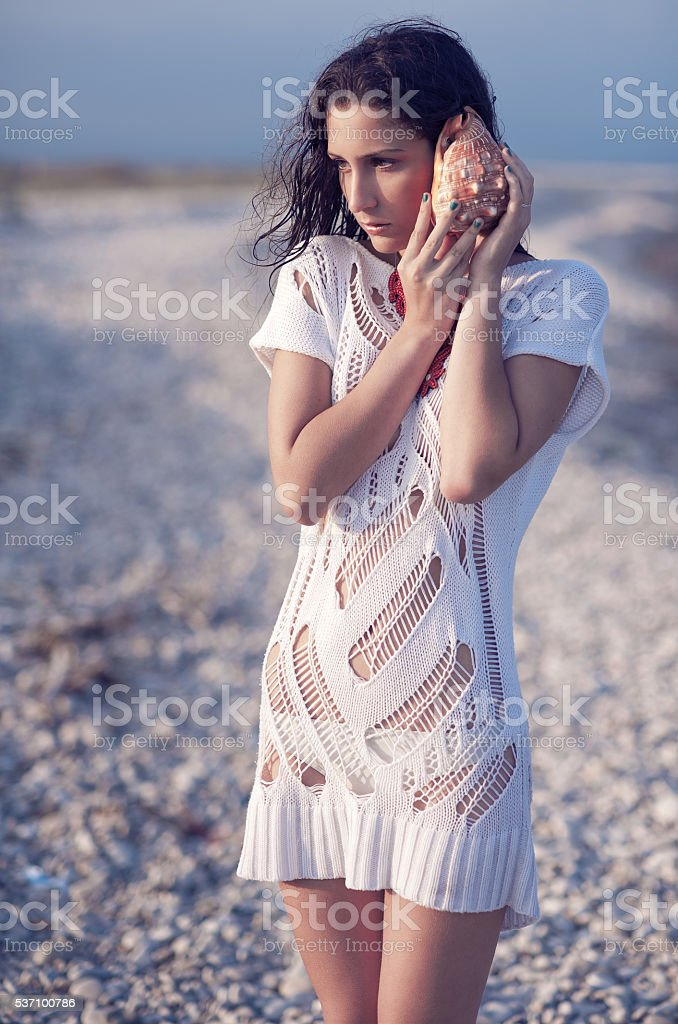 Woman in the beach listening to seashell stock photo