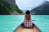 Woman in the boat over beautiful nature environment