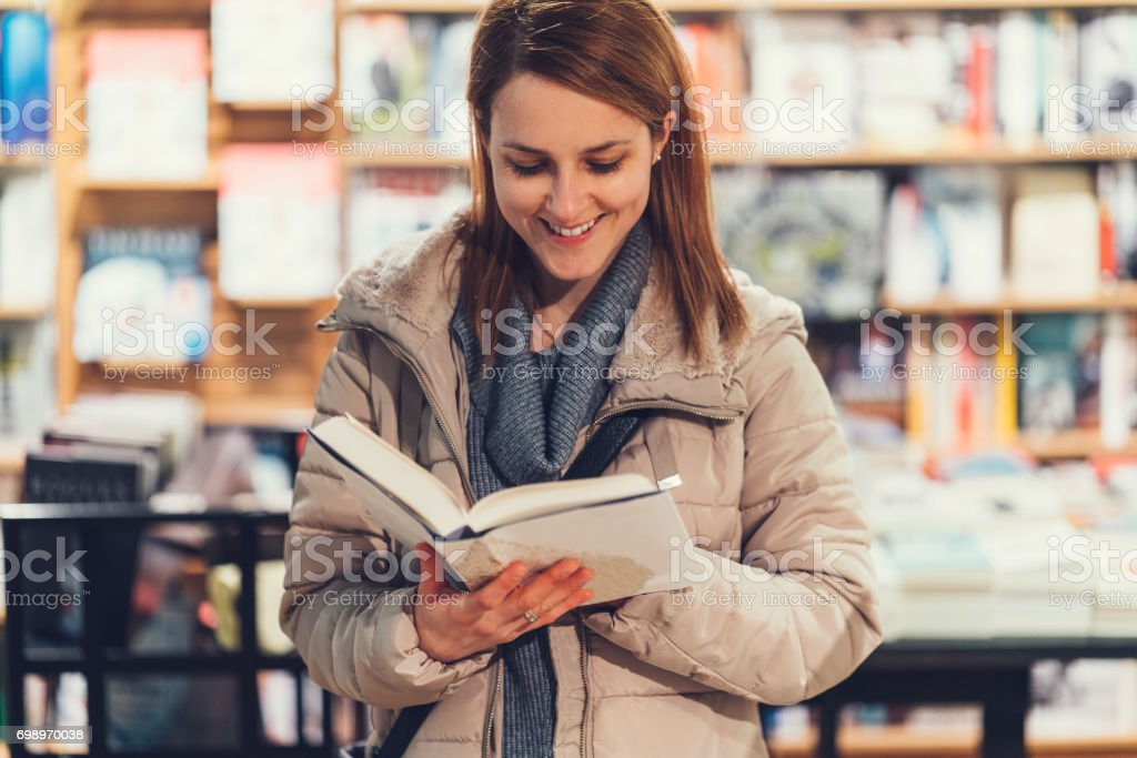 Woman in the bookstore reading a book stock photo