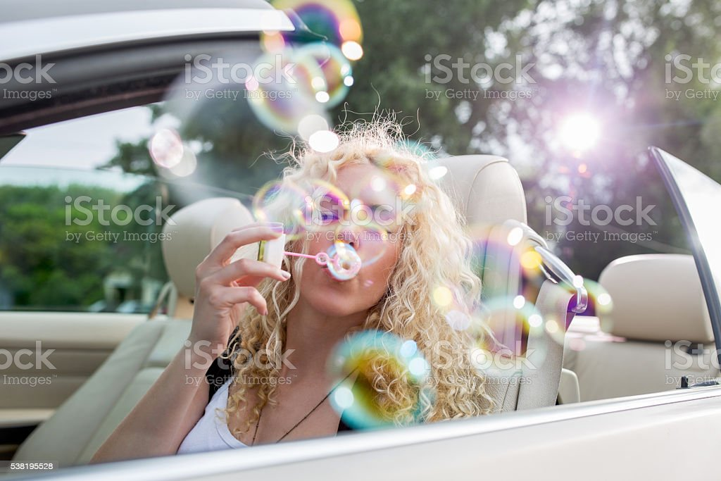 Woman in the car blowing bubble wand. stock photo