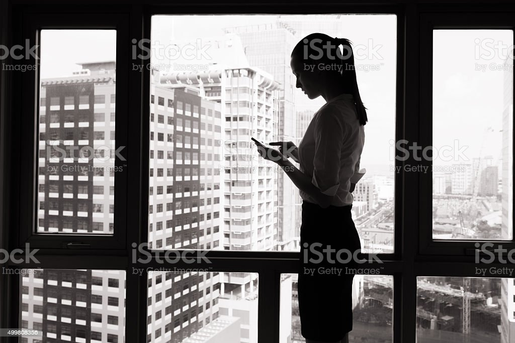 Woman in the city using her phone. stock photo